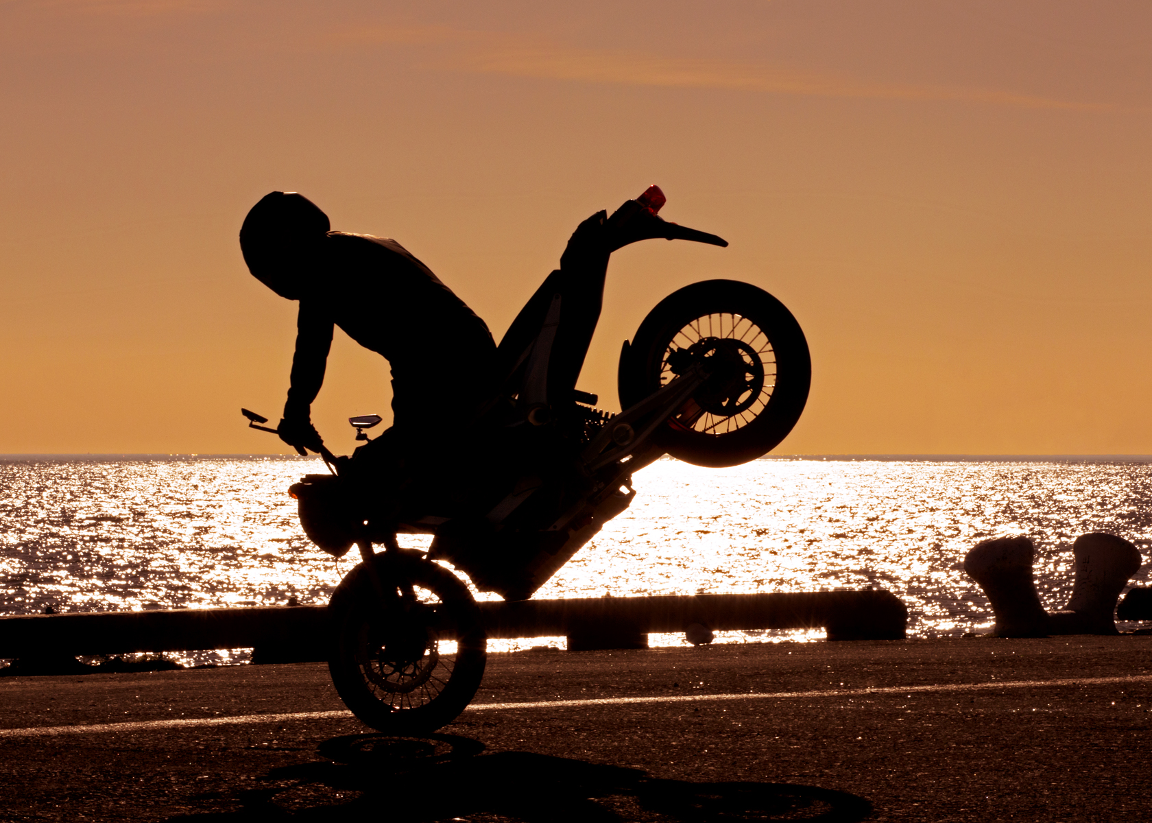 '.2011 Zero S Electric Motorcycle: Wheelie at Sunset by the Pacific Ocean.'